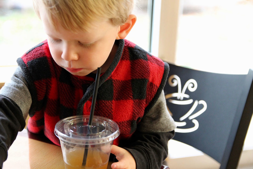 little boy enjoying a local juice while playing a game at the coffee shop